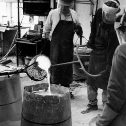 Photo, casting the Bronze Mode in the foundry, pouring of bronze through the gates.